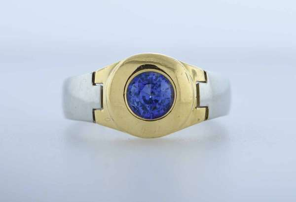18K gold and Sapphire gentleman's ring. Custom made white and yellow gold setting with a bezel set round approx. 1 ct. blue sapphire of a very attractive color, ring size 10, 13.5 grams. Condition: good.  New bidders to Smith's - payment for this lot must be made with cash, bank approved check or wire transfer. NO CREDIT CARDS accepted as payment for this lot.