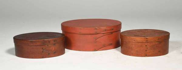 """Three 19th C. Shaker finger boxes, oval 3 finger example, painted red and stained, sizes from left box to right are 6 1/4"""", 7 7/8"""" and 6"""" width - condition: structurally good, stain and chip on lid of box on right, some surface abrasions"""