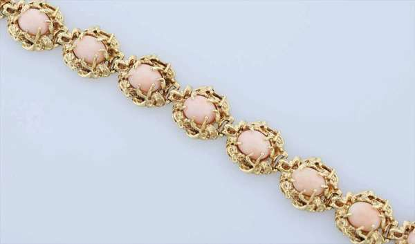 """14k Gold and coral bracelet. Linked design with 9 oval, prong set,cabochon coral stones in chunky 14k gold, 7"""" L , 46 grams. Condition: generally good, appears one prong might be missing. New bidders to Smith's - payment for this lot must be made with cash, bank approved check or wire transfer.  NO CREDIT CARDS accepted as payment for this lot."""