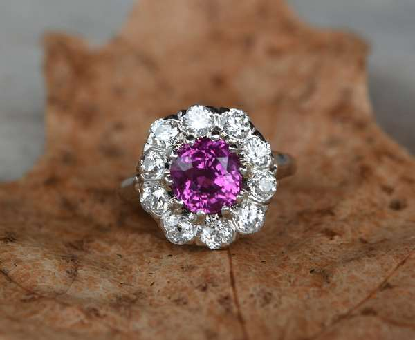 Ruby (or pink sapphire)and Diamond ring in a very desirable style set in platinum. An oval faceted electric rich colored ruby measuring approx. 7.29mm x 7.11mm x 5.27mm deep for a calculated weight of approx 2ct, surrounded with 10 round cut diamonds est. total weight of 1ct, ring size 6, 6 grams. New bidders to Smith's - payment for this lot must be made with cash, bank approved check or wire transfer.  NO CREDIT CARDS accepted as payment for this lot.