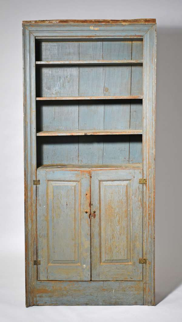 """Late 18th C. country floor cupboard with open top and two lower raised paneled doors, picture frame molding, in blue/gray paint, W 39 1/2 """" x H 86 """" x D 13. Condition: likely later paint surface, probable hinge replacement"""