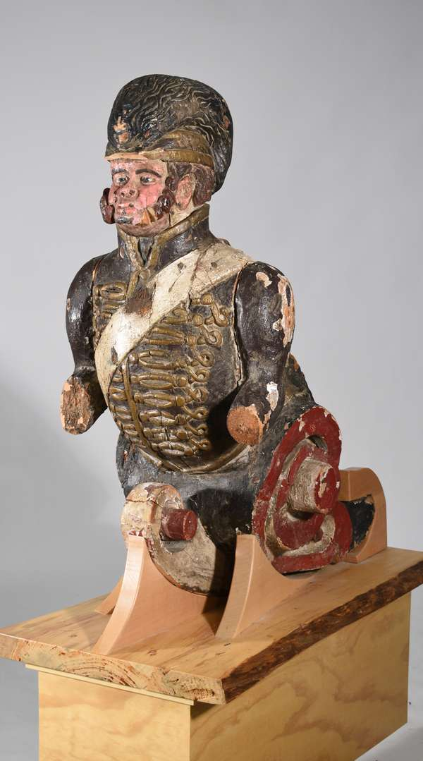 Large antique carved and polychrome painted ships figure head, masthead, supported with early forged iron, believed to be late 18th. C., set on a custom made stand. As the story goes, 'found in a warehouse in Gloucester, MA in the 1930's and acquired by the consignor from the 93 yr. old daughter of the gentleman who discovered it'. This is an impressive piece. Masthead 48''H x 38''L, on stand 68''H.  Condition: expected weathering, paint wear and loss