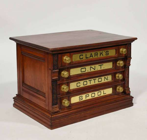 """19th C. four drawer carved Clark's walnut spool cabinet, with gold foil panels reading Clark's O.N.T. Cotton Spool. 23.25""""W. x 15""""D. x 19""""H. -Condition: original condition with some finish loss on top corner, minor flaking on glass panels, overall good"""