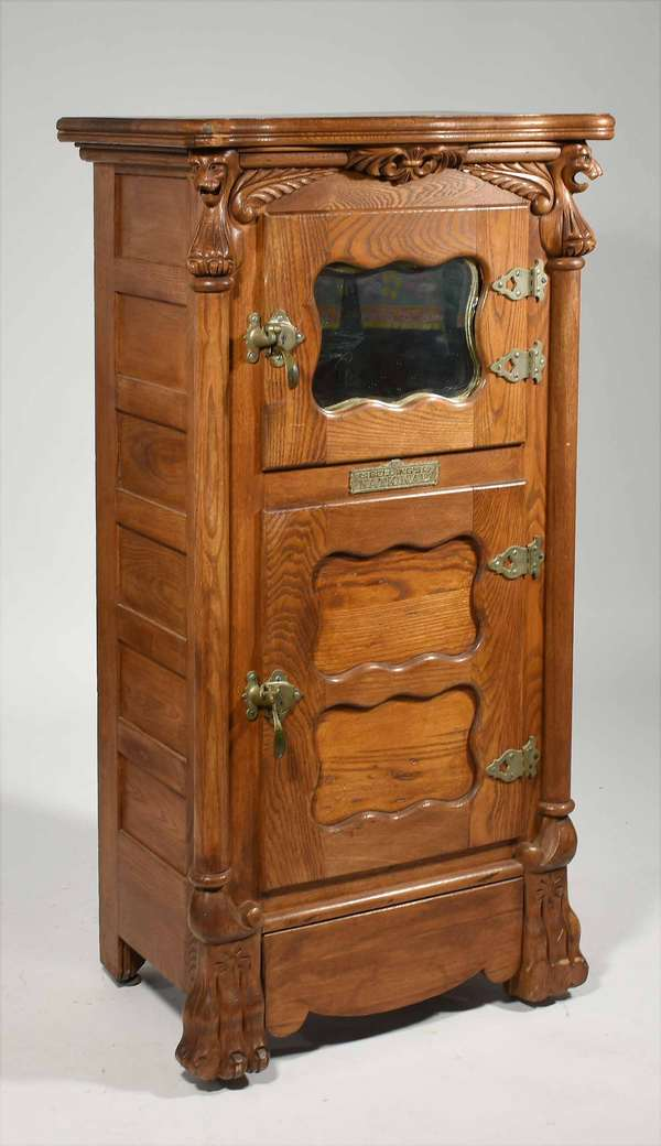 """Carved oak Belding's National ice box with desirable griffin carvings and mirrored door, 52.75""""H. X 26""""W. X 18""""D. -Condition: cleaned surface, loss on upper right shaped corner, scratches in top, interior converted into storage using cedar boards, see images"""