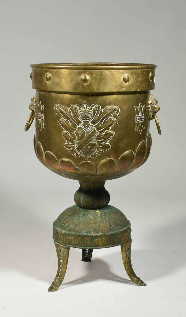 """Embossed antique brass pedestal footed jardiniere, coat of arms and graduated lobes, applied lions head handles, 31""""H. X 18""""Dia. -Condition: dents and discoloration, separation on ring handle"""