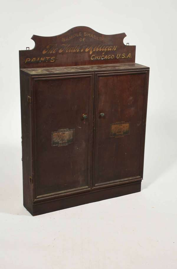 """H & M Paints cabinet, circa 1905, with original decoration, 37""""H X 26.25"""" W X 6"""" D -Condition: scratches signs of use, separation in laminate on crest"""