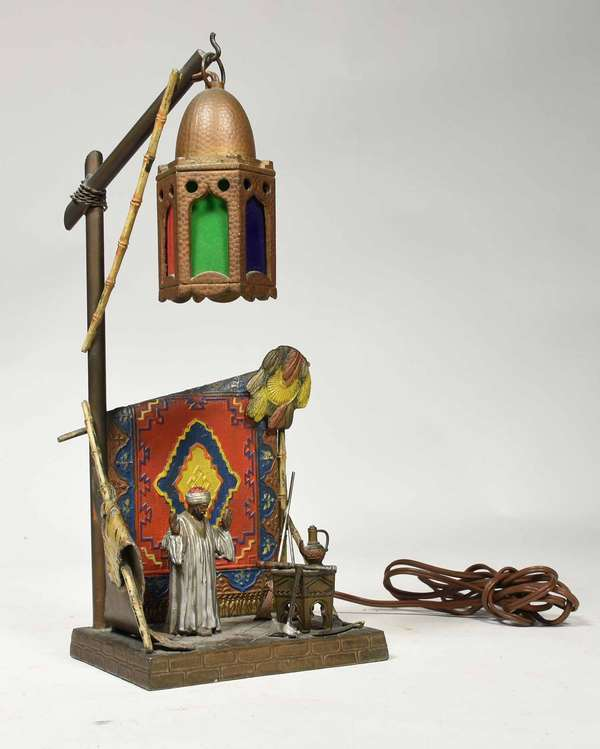 """Eastern tourist lamp made of white metal in the manner of Bergmann, paint decorated depicting figure in an interior, 14"""" H X 6"""" W X 5"""" D. -Condition: probable re-braze/solder on back frame support holding rug, some paint loss"""