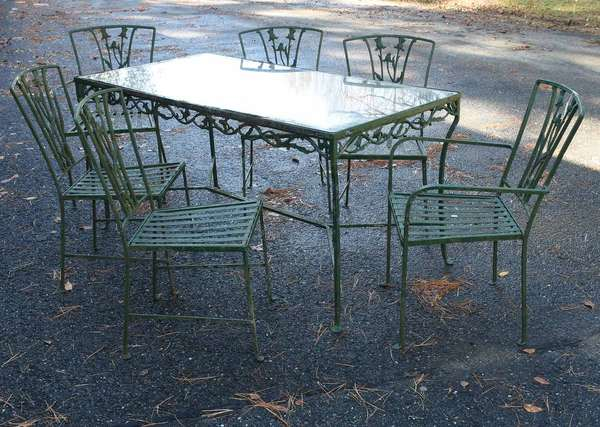 Good 7 piece wrought iron patio set with thistle blossom motifs, glass top table and set of six matching chairs, two arm and four sides. -Condition: stored for many years and showing signs of age, no cushions, flaky green paint