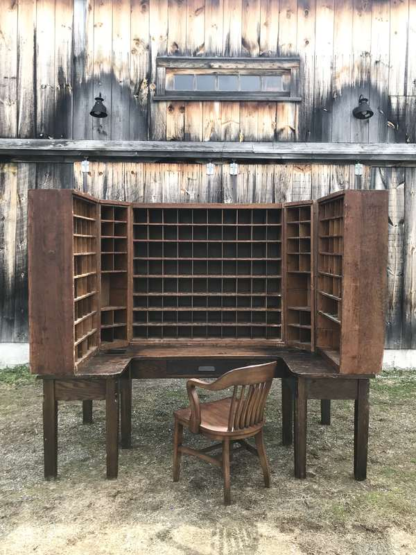 """Unique 20th C. Oak multi-sectional Post Office sorting desk with removable cubby units on desk top, stamped on bottom, White River Jct., VT, 1935- along with vintage chair - unit when set-up, 91"""" width X 75.75"""" H X 48"""" D. -Condition: surface abrasions throughout, some missing cubby dividers, Other signs of use and wear"""