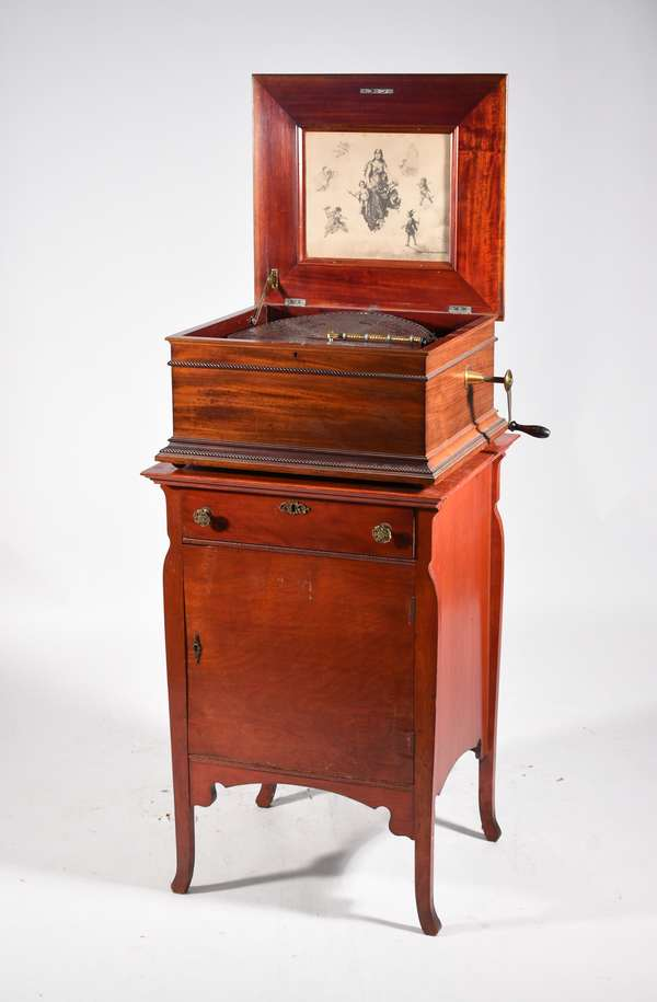 """Regina music box on stand, mahogany single comb box works well with 10 15.5"""" disc size 11"""" H x 21""""W 19""""D, sitting on a birch cabinet base 34:H x 23""""W x 21""""D. -Condition: music box has very good sound, no missing teeth, cases with some abrasions"""