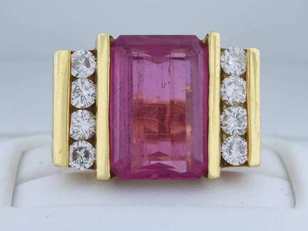 Contemporary 18kt yellow gold ring set with approx. 7.91 ct. hot pink tourmaline (slightly included, light scratches) accented by approx. 1.0 ct. tw. round brilliant cut diamonds (G-H-SI), sz 7, 15.5 gr.  Condition: good condition, pre-owned, expect signs of normal use, slightly loose center stone.