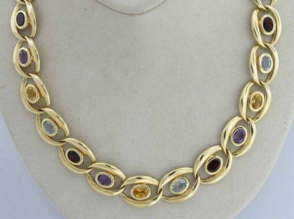 Contemporary 14kt yellow gold chain necklace set with approx. 20 cts. of oval amethyst, garnet, blue topaz, citrine and amethyst, 15 mm wide and is 17 in. long, tongue clasp w/ figure eight safety clasp, 52.3 gr.  Condition: preowned, expect signs of normal use.