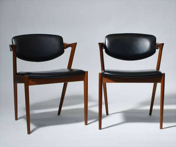 "Kai Kristiansen (Danish, B. 1929). Pair of Teak Dining Chairs, Model # 42, 1960's. With black leather upholstery, assembled in Canada, total height 29 1/4"" seat height 17 1/2"".  Condition: In very fine condition with minimal scuffs and scratches. The arms and legs with light wear. One of the rear chair legs with professional repair near the seat frame. The leather upholstery in very fine condition with no issues detected."