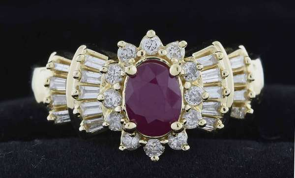 14kt yellow gold ruby and diamond ring approx. .50ct oval slightly purplish red ruby (heavily included) set with approx. .75ct tw round brilliant cut and baguette cut diamonds (H-I-SI), sz 7 1/2, 5.6 grams.  Condition: very good, preowned, expect signs of normal wear.
