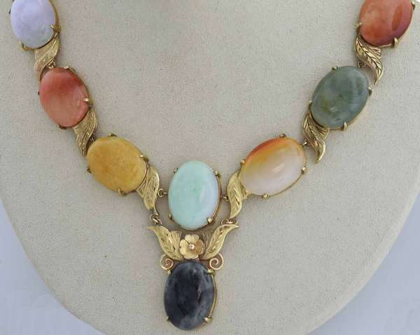 14k yellow gold necklace with leaf and floral motif set with ten multi-color jade cabochons in the tones of dark and light green to mottled black, colorless, orange, gold and very light purple, each measures approx. 15 x 20 mm, approx. 140 ct. tw., 17 1/2 in. long, 43.2 grams.  Condition:  good, preowned, expect signs of normal wear.