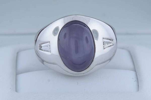 14kt white gold star sapphire ring accented by approx. .25 ct. tw. tapered baguette diamonds (G-VS), six ray star approx. 9 ct. oval cabochon, very light slightly grayish blue, sz 6 1/2, 15.3 grams.  Condition: very good, preowned, expect signs of normal wear.