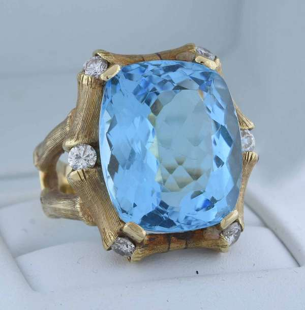 14kt yellow gold bamboo design ring set with an approx. 22 ct. modified brilliant cushion cut blue topaz, accented by approx. 1.0 ct. tw. round brilliant cut diamonds (G-H-VS-SI), sz 8, 15.3 grams.  Condition: good, preowned, expect signs of normal wear (stone lightly scratched).