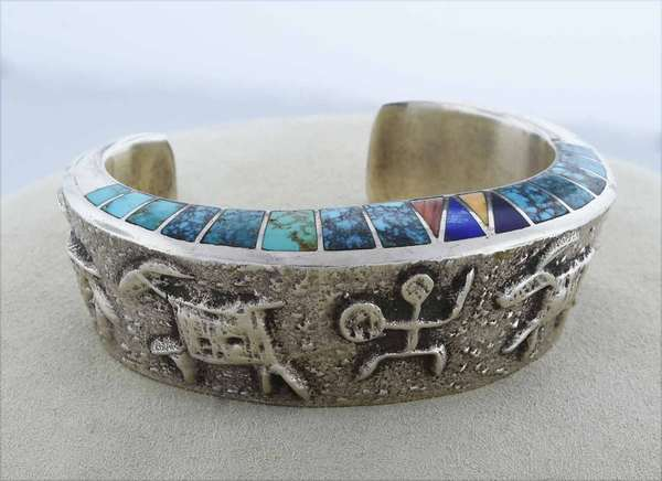 Signed Lonn Parker, Navajo silver cuff featuring petroglyphs and inlay of mostly turquoise and spiny oyster, 15-25 mm wide, 93.7 grams.  Condition:  very good, preowned, expect signs of normal wear.