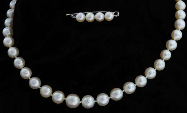 "White graduated cultured pearl necklace fastened by a 14kt white gold pearl clasp set with three small single cut round diamonds, 20 3/4 in. long. The pearls are round to near round with good luster and pink orient, range from 7-10 mm in diameter, includes 1 1/4 in. pearl ""safety pin"" with four, 6 mm white cultured pearls.  Condition: very good, preowned, expect signs of normal wear."