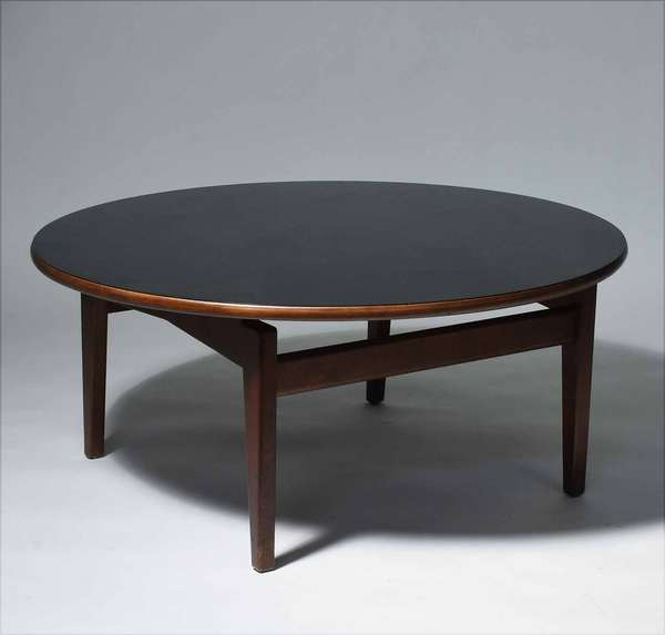 "Jens Risom (Danish, 1916 – 2016). Round walnut coffee table with black laminate top, 1960's. With partial designer's label, 16"" H, 36"" Dia.  Condition: In overall fine condition. Some surface scratches to laminate. Minimal light scuffs to two of the legs."