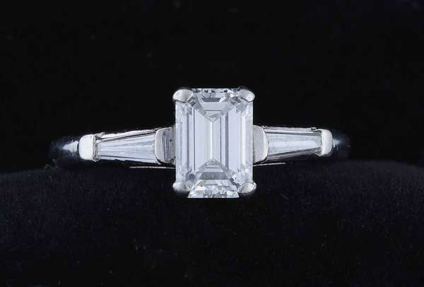 Fine 1 ct emerald cut diamond ring, set in platinum an emerald cut diamond measuring 7.11 x 5.05 x 3.2 mm, est weight of 1.04 ct, est color G and clarity VS1, with diamond baguettes rings size 7.  Condition: very good.