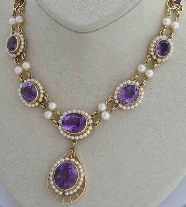 "14k gold amethyst and pearl necklace, containing 8 faceted amethyst stones the largest measuring 12.94 x 15.92 mm all encircled with pearls on a 14k yellow gold chain, approx 16""-17"" chain with a 2"" drop pendant, 32.2 grams.  Condition: good."
