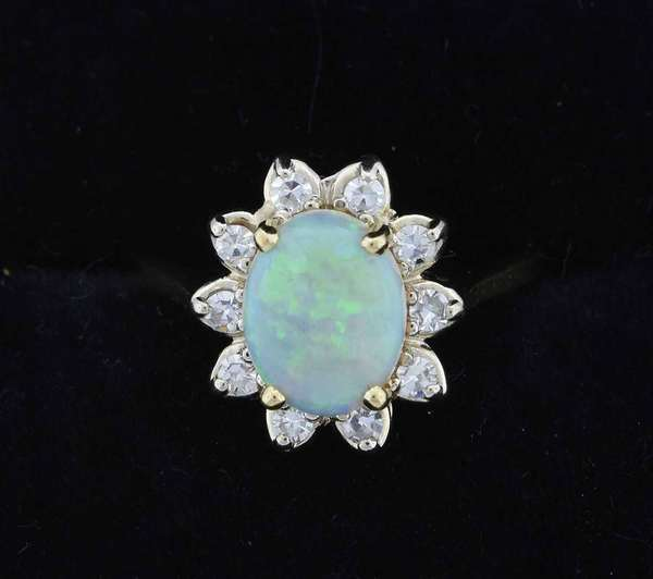 Lady's 14k yellow gold ring set with approx. 1.0 ct opal accented by approx. .20 ctw single cut diamonds (H-VS) size 6, 3.7 grams.  Condition: very good