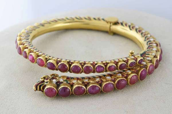 "Impressive 18k gold and ruby snake bracelet, a hinged example with 44 cabochon rubies with an estimated total weight of 10- 12 cts, ranging in size from 2.5mm up to 5mm diameter, the sides of the bracelet with red, green and white enamel decoration, weight 81 grams , inside diameter 2.25"" outside 3"". Condition: structurally good, some enamel loss some rubies with fissures and inclusions"