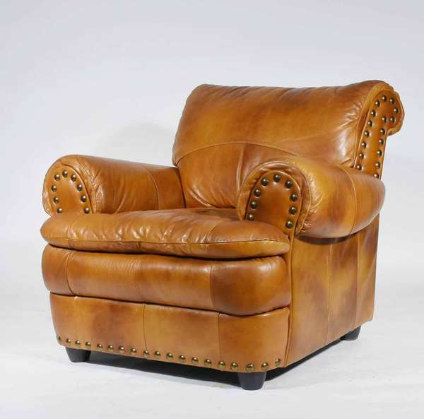 "Italian leather club chair, brass studded in saddle brown leather. Height 36"", seat height 19"", width 39"", depth 41"".  Condition: Some slight discoloration on seat, arms - scratch on proper left side, see image"