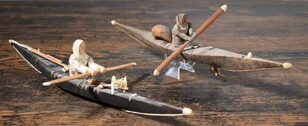 "TWO EARLY INUIT KAYAKER FIGURINES, CA. 1900-20. The black kayak with white figure, 15"" L, the brown kayak and figure 12"