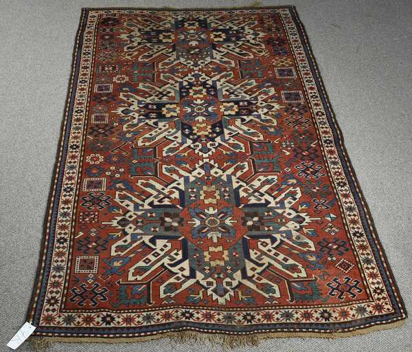 "ANTIQUE EAGLE KAZAK RUG, CA. 1900. With three repeating central medallions on a brick red field with green, navy and tan accents. 5ft. 1"" x 9ft. 1"".  Condition: light field wear, fraying to the fringe on one side. General soiling."