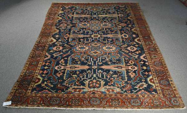 "ANTIQUE HERIZ ROOM-SIZE RUG, CA. 1925-30. With all over design on a navy field with powder blue, salmon, light green, and brick red accents. 9ft. 3"" x 11 ft. 8"".  Condition: very light even wear to edges and general soiling."