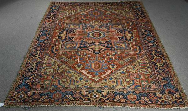 "ANTIQUE HERIZ ROOM SIZE RUG, CA. 1925-30. The center medallion on a brick red field, with green, blue, and tan accents. 9ft. 3"" x 11 ft. 5"".  Condition: light wear to the pile, significant wear to the fringe. General soiling.  Est. $800-1,200"