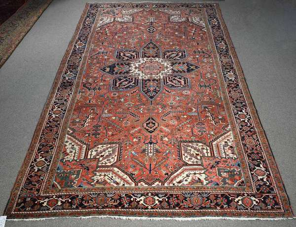 "ANTIQUE HERIZ RUG, CA. 1920-30. The center medallion on a brick red field with powder blue, navy, ivory and green highlights, 9'4"" x 15'7"".  Condition: good with negligible wear."