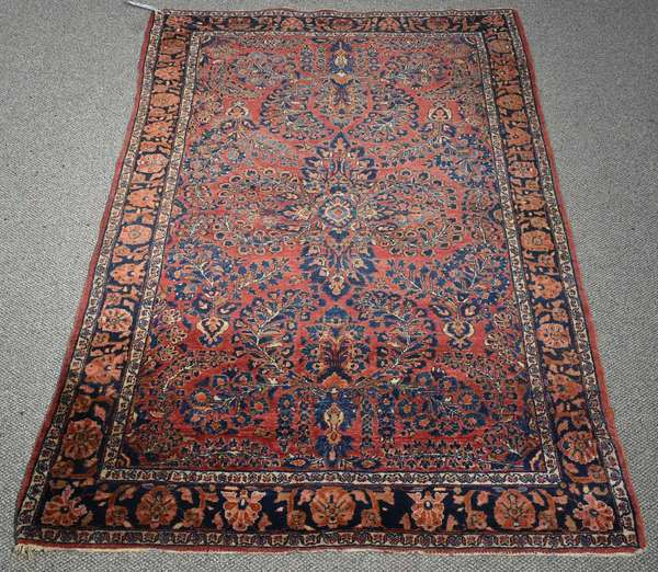 "ANTIQUE SAROUK SCATTER RUG. With three repeating medallions in cobalt, ivory, light blue, beige, and pink threads on a brick red field surrounded by a floral border, 6'5"" x 4'4"".   Condition: general soiling and light edge wear."