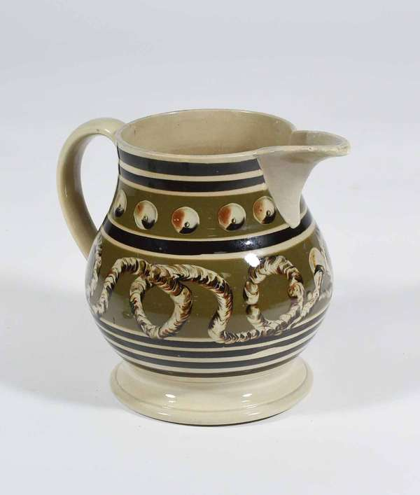 "19TH C. MOCHAWARE PITCHER. Earthworm and coin spot decoration. Dark brown and olive green banding. 7.5"" H X 9"" W. Condition: overall good with some cosmetic blemishes including three flaked losses of green band decoration, 1/2"" & 3/4"" (on front under spout) staining on interior and on spout, crazing."