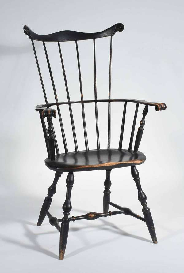 "18TH C. NEW ENGLAND FAN-BACK WINDSOR ARM CHAIR. A refined example with well carved rolled knuckle arms and fan, a saddle seat on a stretchered and vase & ring turned base. An old surface showing a black paint over remnants of green/red stain. 43.5"" H X 25.75"" W X 19.5"" D X 17.25"" seat height.Condition: old farm repair (bracing) on underside of proper right arm, current fracture and looseness at right wrist, very slight racking/looseness, some age splitting but stable."