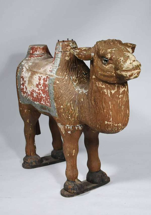 "LATE 19TH C. CAROUSEL CAMEL. Carved and painted pine in standing position, set with glass eyes, 36""H x 46"" L. Condition: Appears to be original paint, however heavy paint wear around the seat, light wear throughout, humps missing padded tops."