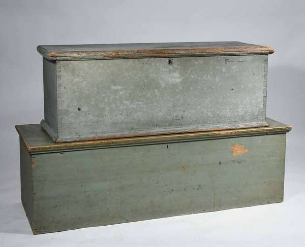 "TWO EARLY PAINTED BLANKET BOXES.  The smaller an 18th C. example with dovetailed construction in old blue/gray paint, 18"" H x 16"" D x 49"" L. The larger box of the early 19th C., six board with square head nail construction in old light green paint, 18"" H x 20"" D x 58"" L. Condition: Paint wear scratches and chips."