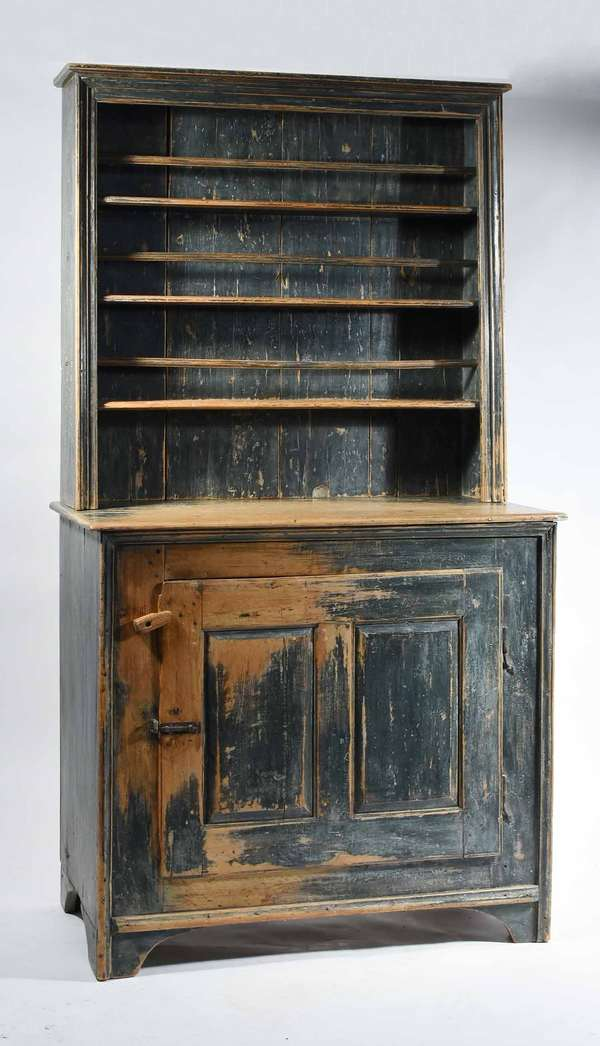 "19TH C. AMERICAN CANTED-BACK PAINTED FLOOR CUPBOARD. In two parts, painted in a blue gray paint, open top canted back with plate guards, bottom with one single raised panel door, iron latch and turned knob, 80"" H x 20"" D x 43 1/2"" L. Condition: Structurally sound with repairs and replacements."