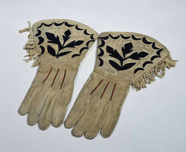 "BUFFALO BILL DEERSKIN GLOVES. Thread sewn gloves purportedly owned and used by Col. W.F. Cody/Buffalo Bill, decorated with black felt, green/pink needlework strips and fringe, 15"" L X 9"" W at cuff. Condition: Some dirt build up and soiling, supple hide."