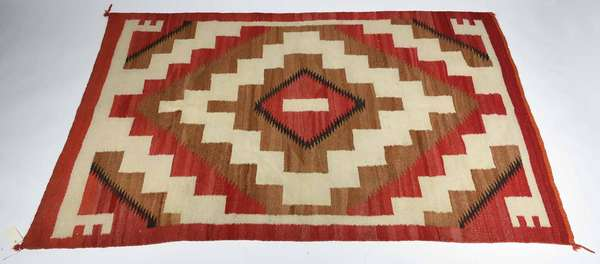 "ANTIQUE NAVAJO WOOL BLANKET. Dark/light brown, ivory and red with a burnt orange upper border, 68 1/2"" x 43 1/2"". Condition: overall good with small stitched repairs (see images) some minor soiling/staining."