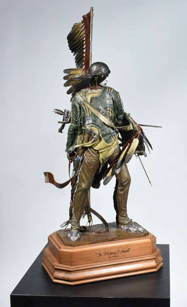 "DAVE MCGARY, BRONZE 'IN VICTORY I STAND', #7/60. Cold painted bronze of a Native Am. warrior, mounted on an engraved swiveling walnut base, bronze signed ""Dave McGary 2001 7/60"", 19.5"" H (Bronze) 23.25"" H overall.  Condition: overall very good, slight bending to feathers and arrow."