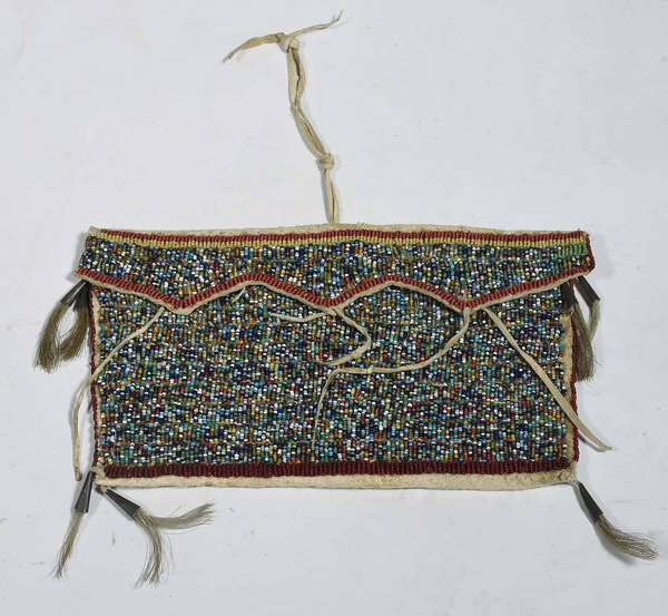"19TH C. BEADED NATIVE AM. FLAPPED BELT BAG. Multi-colored sinew sewn beads, with tin cones and horse hair drops, 5 1/2"" H x 10"" L.  Condition: leather is supple and in overall good condition."