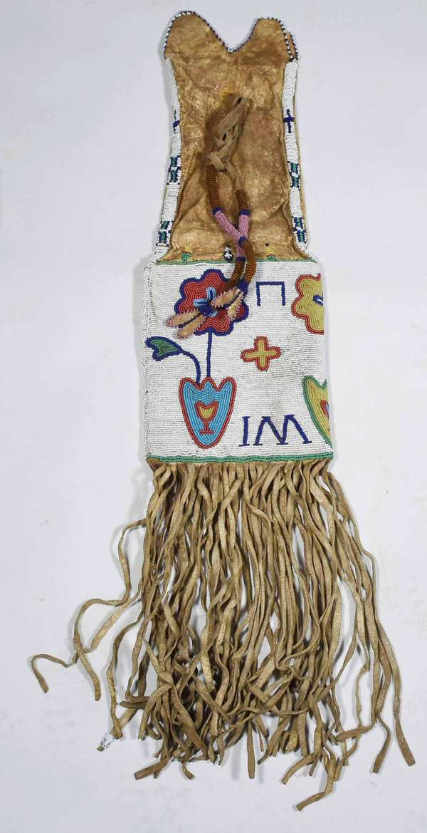 "19TH C. SOUTHERN PLAINS BEADED PIPE BAG. Sinew sewn native leather with multi-color motifs on white ground, 30""H. x 6.5""W.  Condition: supple leather, overall good."