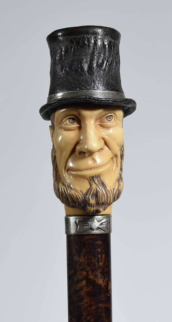 "EARLY 20TH C. ABRAHAM LINCOLN POP-UP TOP HAT CANE. The leather top hat with push-down motion and spring-loaded release button behind the carved bone head, with sponge painted wooden shaft, overall 40"" H.   Condition: In very good condition with little signs of use. The leather top hat with light wear. Some negligible abrasions and faint adhesive mark to the bottom of the shaft."