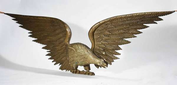 "IMPRESSIVE CARVED LATE 19TH C. SPREAD-WINGED AM. EAGLE WALL PLAQUE. Monumental scale eagle with antique bronze paint, 27"" H x 98"" L x 5"" D. Provenance: Acquired by seller in 1993 from Historic Smithville Village, in Smithville, NJ. This eagle hung on a wall by a stairway in the main building.  Condition: In overall good, structurally sound condition. Note that the wall plaque is constructed of sectional pieces, particularly the wings and shoulders, and that there is some minor separation of these pieces, but they are stable. Paint wear and chips throughout with an area of green paint near the eagle's leg. Drill holes on reverse from prior hanging."