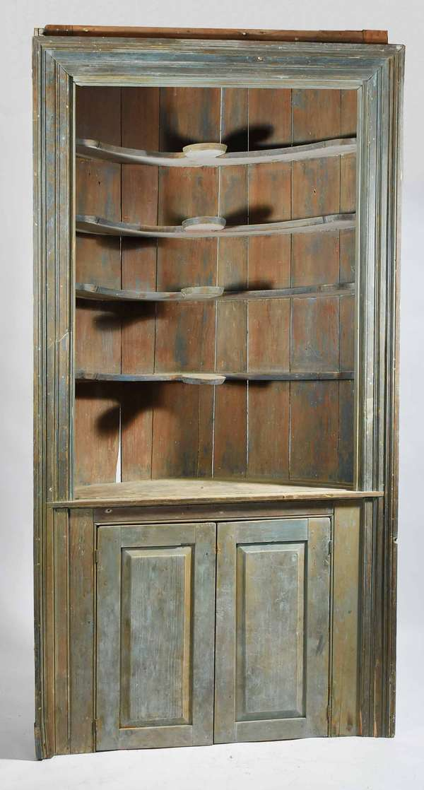 "18TH C. ARCHITECTURAL BARREL BACK CORNER CUPBOARD; dry scraped blue paint, open top with scalloped shelves over two raised paneled doors below, applied picture frame molding, 46""W x 88""H x 24"" DCondition: cracks in protruding lobes on upper shelves, showing consistence signs of use and wear appraise for age of cupboard including shrinkage splitting and separation,  abrasions, etc. repaired lower right side molding."