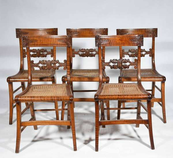 "SET OF 5 FEDERAL TIGER MAPLE CHAIRS. ca 1825-35, with carved backs, saber legs and cane seats older finish and medium to strong tiger maple, 34""back H x 17""W x 17.5"" seat H. Condition structurally sound with some old repairs one seat with puncture."