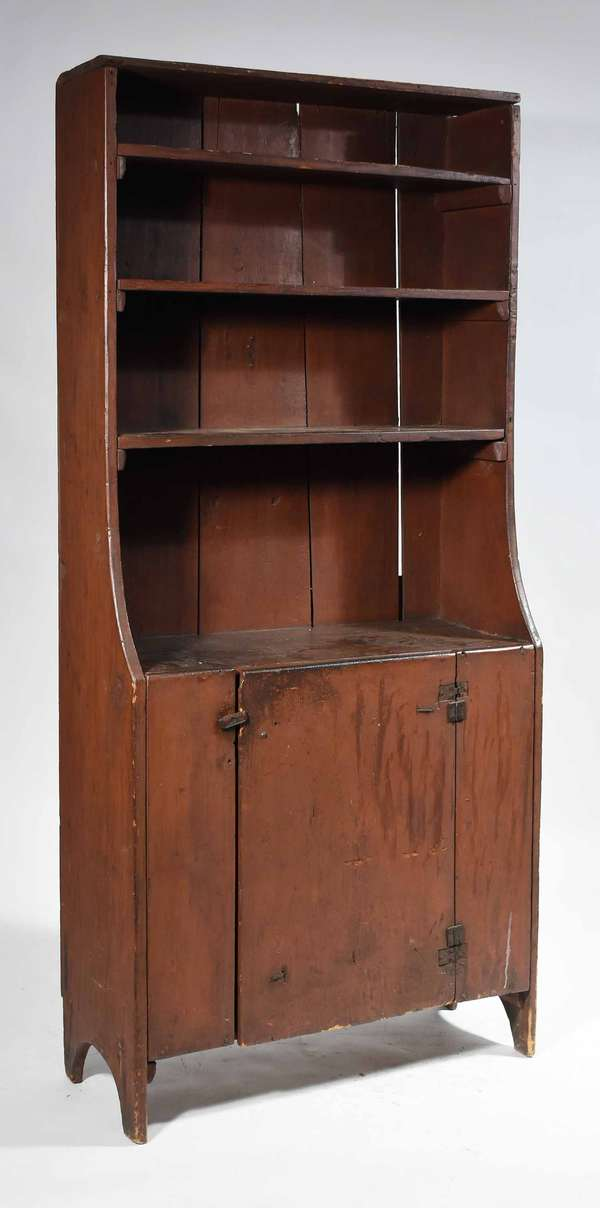 "18TH C. NEW ENGLAND OPEN TOP FLOOR CUPBOARD. Diminutive pine cupboard with an old red paint. Top with three fixed shelves over a single hinged door below revealing a single fixed shelf. Solid sides with cut out at base. 70"" X 31.5"" W X 13.25"" D. Condition: shrinkage a warping commensurate with age, two sets of antique hinges on door, surface abrasions."
